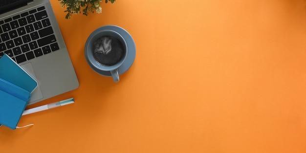 Imagem da vista superior do laptop do computador, colocando sobre a mesa de trabalho colorida, rodeada por xícara de café, nota, caneta e planta em vaso. conceito de local de trabalho em ordem.