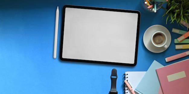 Imagem da vista superior do tablet de tela em branco branco colocando na mesa de trabalho colorida que cercada por canetas, cadernos, smartwatch, xícara de café, porta-lápis e vaso de plantas. área de trabalho desordenada.