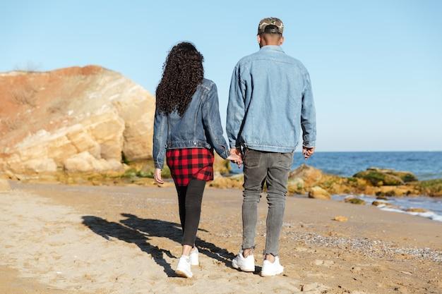 Imagem da vista traseira do casal apaixonado africano caminhando ao ar livre
