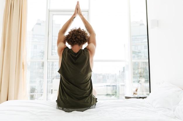 Imagem da vista traseira do homem encaracolado, sentado no alongamento da cama.