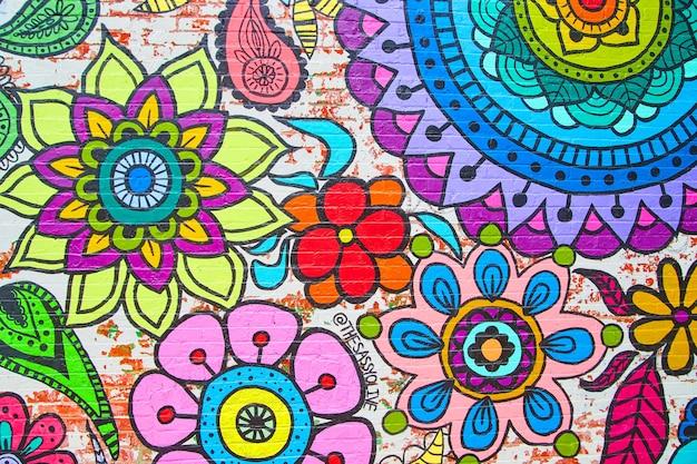 Imagem das cores do arco-íris de flores em um mural de parede de tijolos