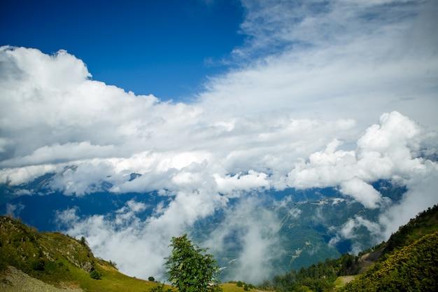 Imagem das encostas das montanhas com vegetação, céu nublado