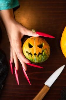 Imagem das mãos de uma mulher com unhas cor de rosa com macaco-abóbora, aranha e faca sentada à mesa de madeira
