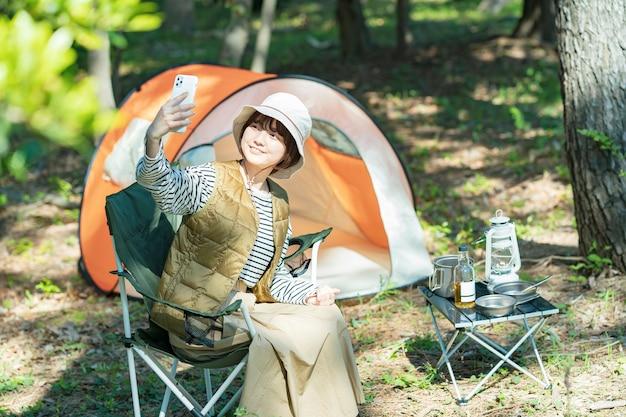 Imagem de acampamento solo - jovem operando um smartphone