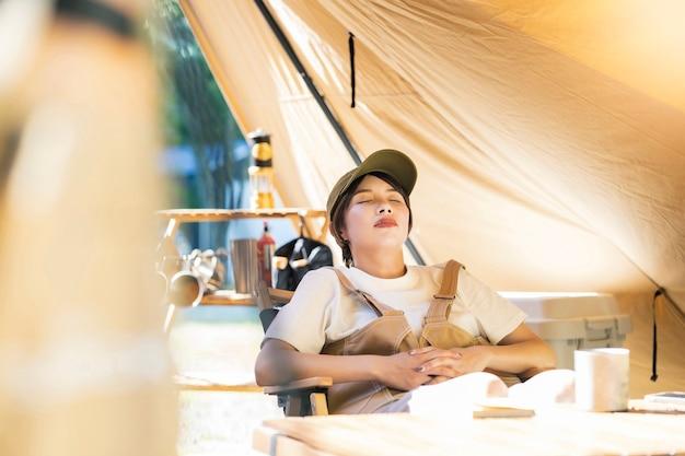 Imagem de acampamento solo - jovem tirando uma soneca em frente a uma tenda