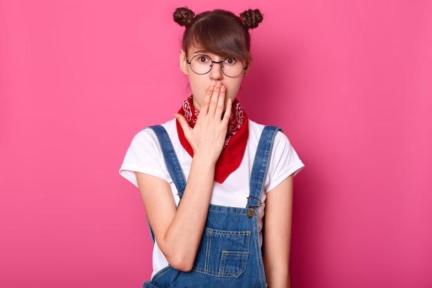 Imagem de adolescente de cabelos escuros surpresa com banches engraçados, cobre a boca com a mão, veste camiseta, macacão, óculos e bandana, olha com os olhos bem abertos, ouve notícias chocantes, isoladas na parede rosa.