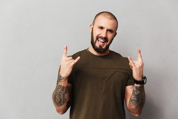 Imagem de alegre cara sem pêlos com barba e bigode, sorrindo e mostrando sinal de pedra, isolado sobre a parede cinza