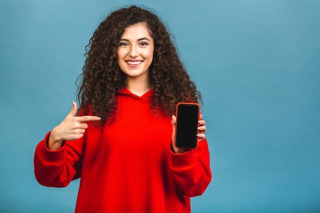 Imagem de alegre espantado jovem mulher caucasiana encaracolada mostrando o visor do telefone móvel.