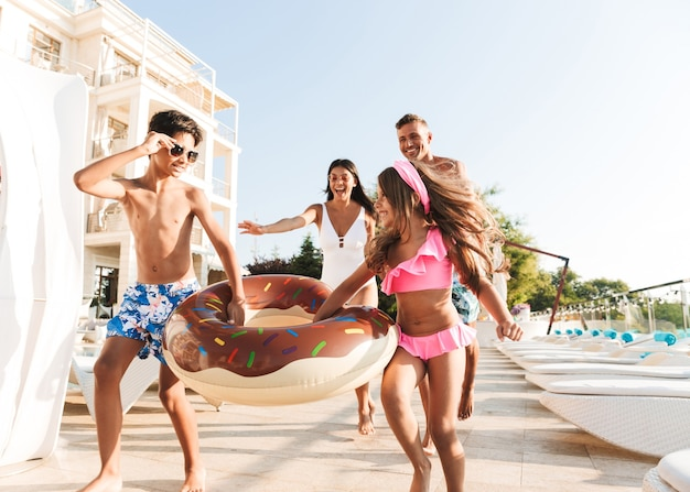 Imagem de alegre família caucasiana com filhos, descansando perto de uma piscina luxuosa e se divertindo com um anel de borracha do lado de fora do hotel