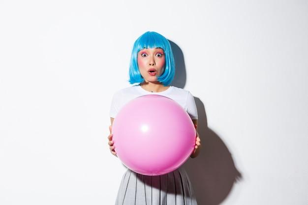 Imagem de alegre menina asiática com peruca azul, comemorando o feriado, vestindo roupas para festa de halloween