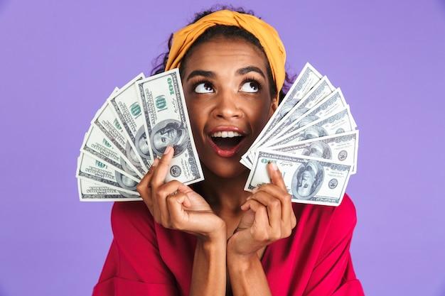 Imagem de alegre mulher africana em vestido segurando dinheiro e olhando por cima da parede roxa