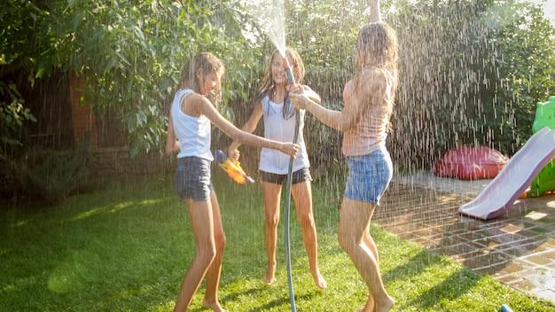 Imagem de alegres garotas rindo com roupas molhadas, dançando no jardim e segurando a mangueira de água. família brincando e se divertindo ao ar livre no verão