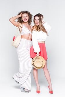 Imagem de altura total de duas meninas atrevidas felizes, melhores amigas se divertindo, rindo no fundo branco.