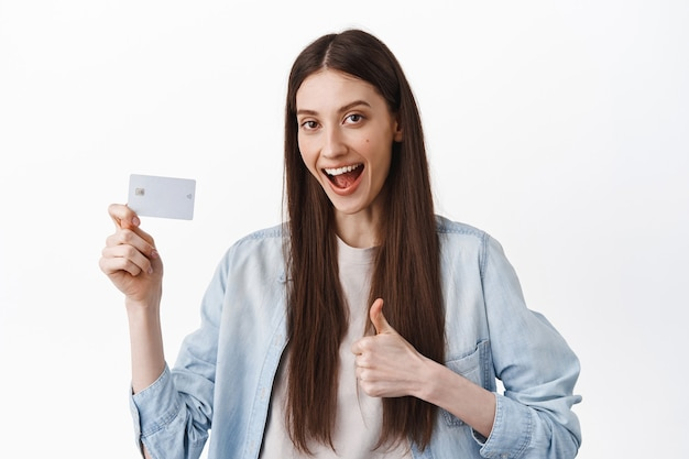 Imagem de aluna dizendo sim, mostrando cartão de crédito e polegar para cima, aprovar e recomendar banco, pagamento sem contato fácil, em pé sobre uma parede branca