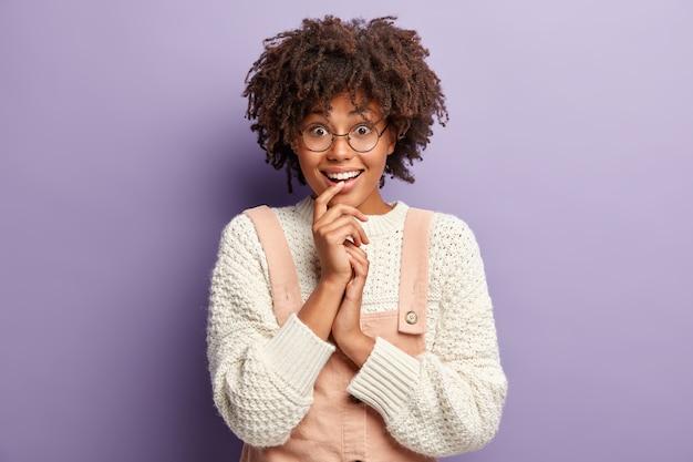 Imagem de aluna otimista com penteado afro, curtindo o fim de semana, expressa boas emoções, veste blusão branco e macacão rosa, ouve informações com expressão alegre