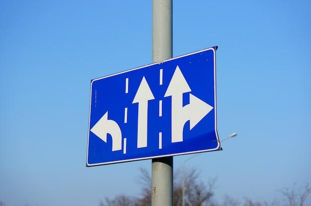 Imagem de ângulo baixo de um sinal de direção azul com setas brancas