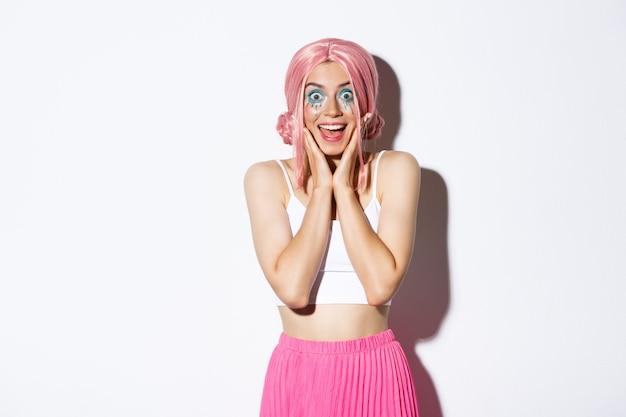 Imagem de animada festeira com peruca rosa e maquiagem brilhante parecendo impressionada, sorrindo e olhando surpresa, em pé.