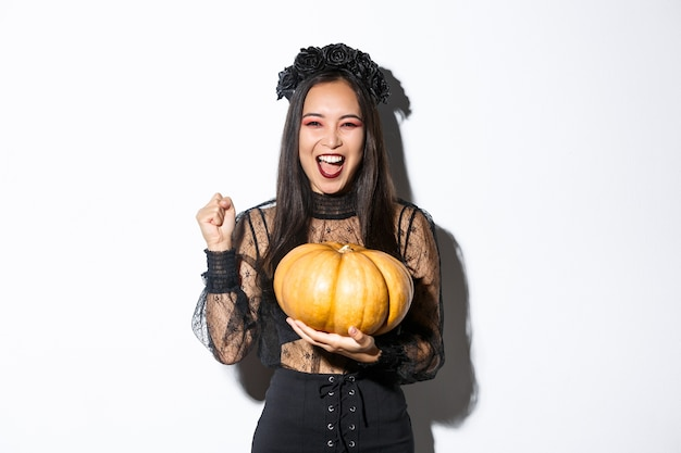 Imagem de animada linda mulher asiática comemorando o dia das bruxas, vestindo roupa de bruxa e segurando uma abóbora, gritando de alegria.