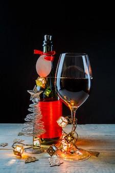 Imagem de ano novo de garrafa com fita vermelha, brinquedos para árvore de natal, copo de vinho na parede escura com guirlanda em chamas