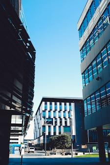 Imagem de arranha-céus modernos com janelas azuis e uma área de estacionamento sob um céu azul