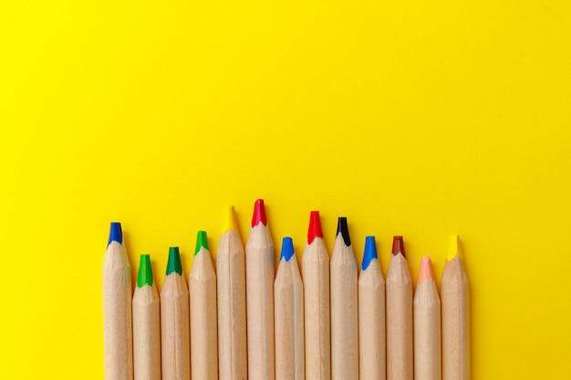 Imagem de arte linha com lápis coloridos amarelos sobre fundo amarelo para papel