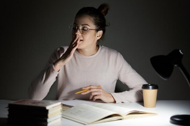 Imagem de atraente estudante espreita boceja com os olhos fechados