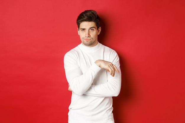 Imagem de atrevido homem caucasiano de suéter branco, olhando pensativo para a câmera, fazendo escolha em pé.
