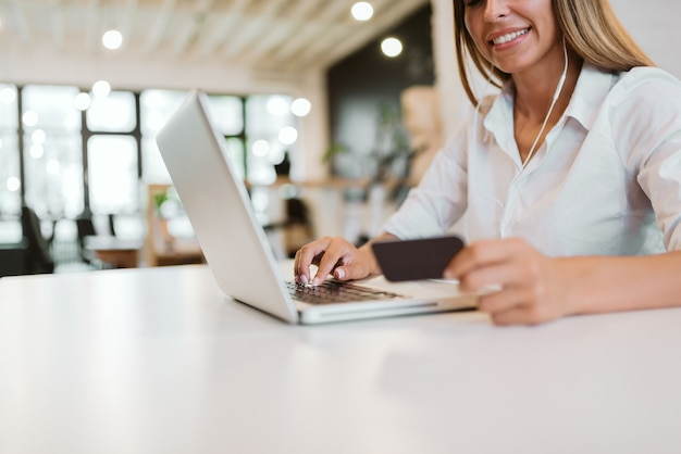 Imagem de baixo ângulo de jovem mulher comprando on-line com cartão de crédito. copie o espaço.
