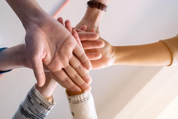 Imagem de baixo ângulo de pessoas colocando as mãos na pilha juntas