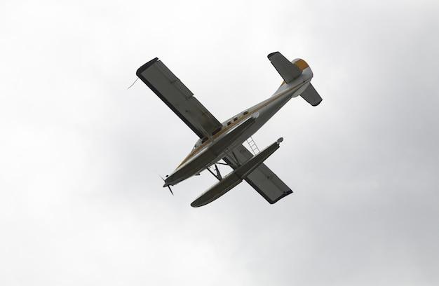 Imagem de baixo ângulo de um hidroavião voando sobre o céu claro