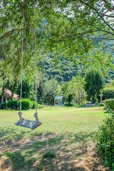 Imagem de balanço de madeira debaixo da árvore no jardim