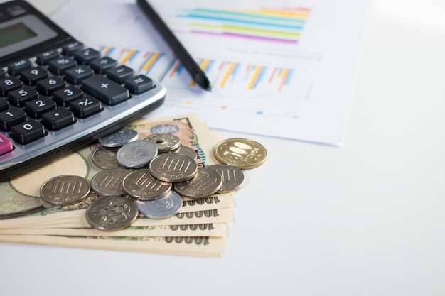 Imagem de banco de 10.000 ienes e muitas moedas com calculadora, caneta e papel