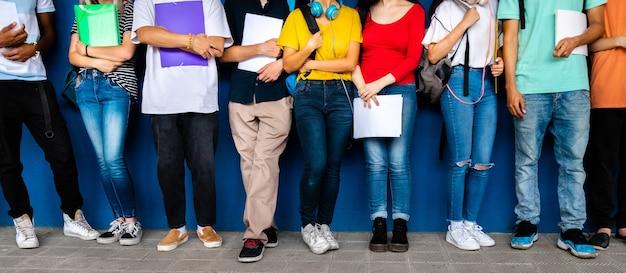 Imagem de banner horizontal de grupo de alunos multirraciais do ensino médio, prontos para voltar para a escola em pé contra a parede de fundo azul. conceito de educação.