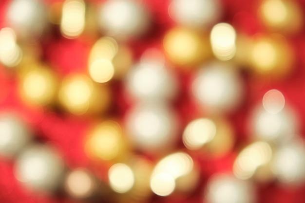 Imagem de bolas de natal brilhantes desfocadas ocupando toda a imagem em fundo vermelho brilhante