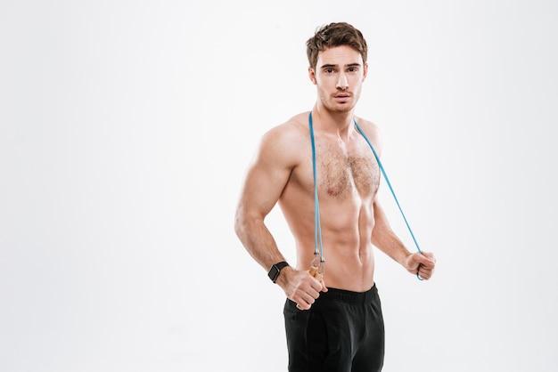 Imagem de bonito desportista em pé com pular corda na parede branca.