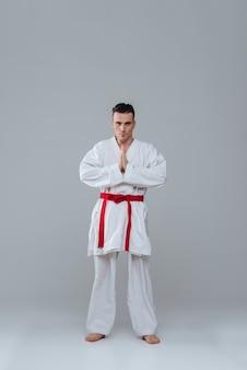 Imagem de bonito desportista na prática de quimono no caratê enquanto posava sobre um fundo cinza. olhando para a câmera.