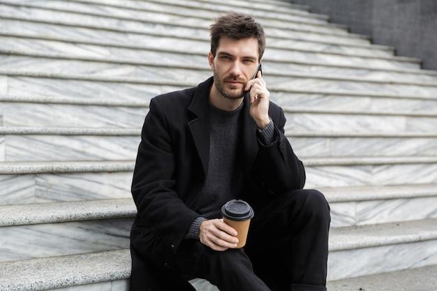 Imagem de bonito jovem empresário sentado ao ar livre, falando por telefone celular, bebendo café.