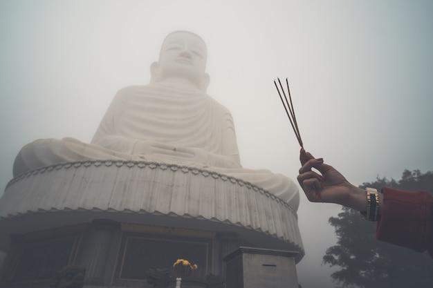 Imagem de buda com incenso. três incensos na mão de uma mulher contra um grande buda no meio do nevoeiro. colina bana. vietnã. danang.