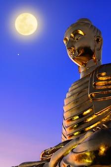 Imagem de buda na cena noturna, a bela estátua dourada tem uma lua cheia com um luar amarelo brilhante no céu azul da meia-noite, escultura que é adoração por budistas no dia importante do budismo, na tailândia