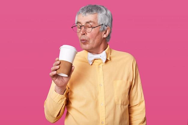 Imagem de cabelos grisalhos sênior na camisa amarela brilhante e gravata branca contém café para viagem