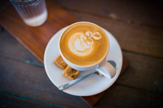 Imagem de café com leite quente com arte em espuma de leite em uma mesa de madeira