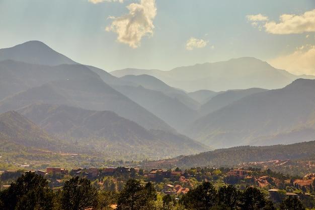 Imagem de camadas de montanhas nebulosas atrás de uma pequena cidade no deserto