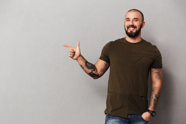Imagem de cara alegre com barba com tatuagens nas mãos, posando e apontando o dedo de lado na copyspace, isolado sobre a parede cinza