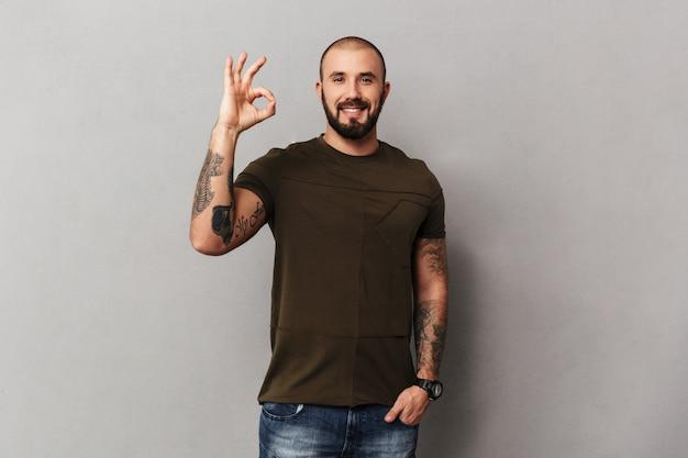 Imagem de cara musculoso com barba com tatuagens nas mãos, posando e mostrando sinal ok, isolado sobre parede cinza