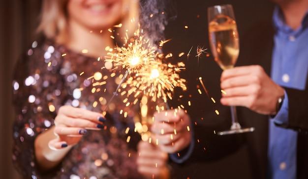 Imagem de casal com taças de champanhe e estrelinhas em fundo preto
