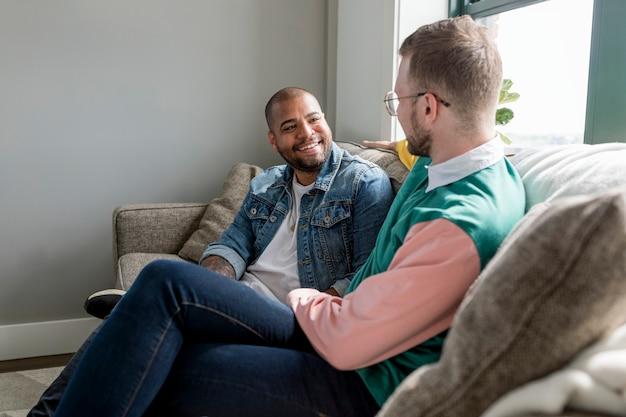 Imagem de casal gay feliz, sentado em um sofá em casa