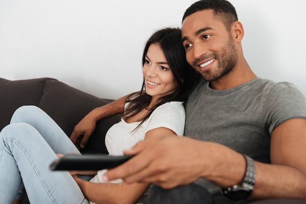 Imagem de casal jovem alegre abraçando e assistindo tv no sofá em casa.
