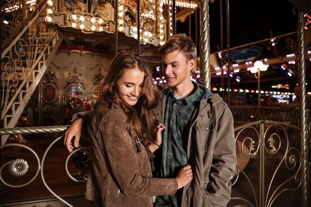 Imagem de casal no parque de diversões.