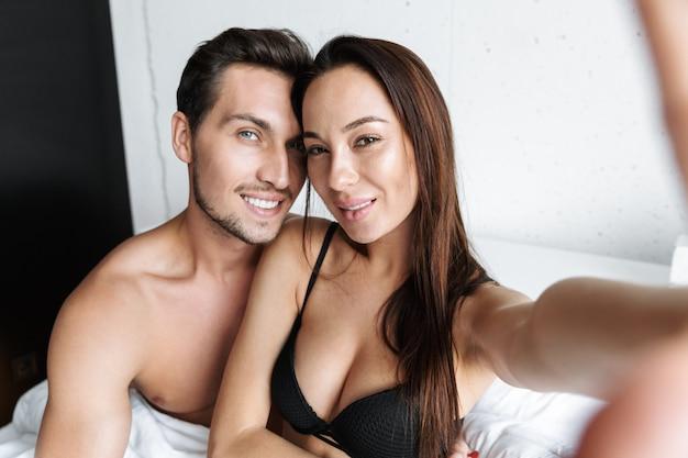Imagem de casal romântico homem e mulher tirando foto de selfie juntos, deitado na cama em casa ou apartamento de hotel
