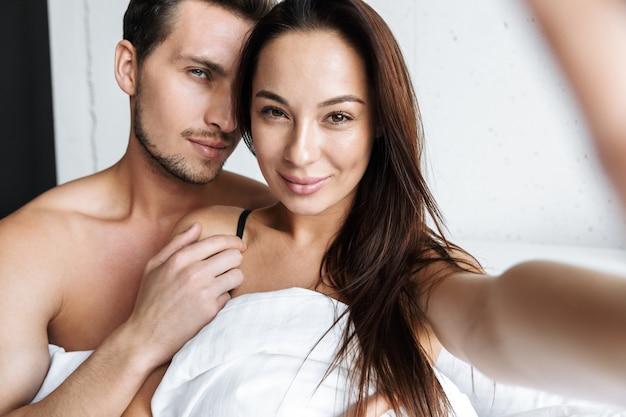 Imagem de casal sexual, homem e mulher, tirando uma foto de selfie juntos, deitado na cama em casa ou em um apartamento de hotel